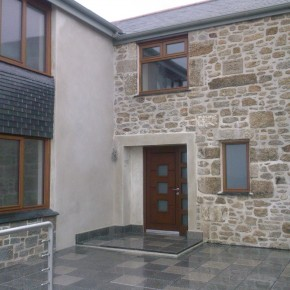 Door alcove in lime . Door surround in lime over an unattractive cast concrete lintel . The wall is rendered block with lime pointing and wet laid vertical slate.