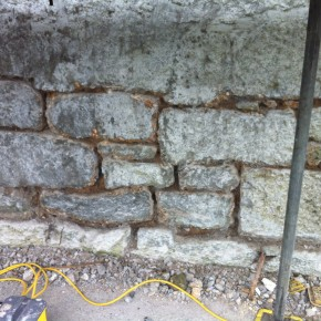 Because the wall had been pointed with waterproof pointing and then tanked with a cement slurry. It made it necessary to remove the pointing to allow the building to breath.